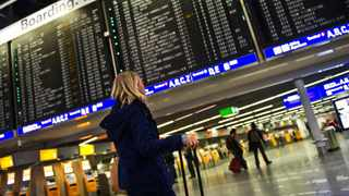 A woman looks at an information board which displays cancelled flights at the airport in Frankfurt, Germany. Picture: AP Photo/dpa,Nicolas Armer)