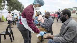 A health worker sprays sanitiser on a man's hands as people undergo screenings for Covid-19 in Lenasia, south of Joburg. South Africa and more than half of Africa's 54 countries have imposed lockdowns, curfews, travel bans or other restrictions to try to contain the spread of the highly contagious new coronavirus. Picture: Themba Hadebe/AP