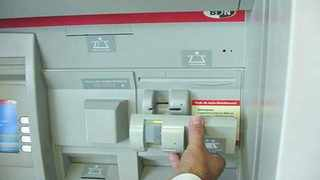 A skimmer is installed on the front of an existing bank card slot.