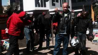 """Bikers carry a wooden coffin with the words """"RIP ETOLL"""" written on the side, as part of a protest against e-tolls outside COSATU house in Johannesburg. Picture: Karishma Dipa/SAPA"""