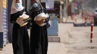 Women hold stacks of bread as they walk along an empty street in Qamishli, Syria, during restrictions to curb the spread of Covid-19. Picture: Rodi Said/Reuters