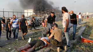 Rescue workers help an injured man at the explosion scene that hit the seaport of Beirut. Picture: Hussein Malla/AP