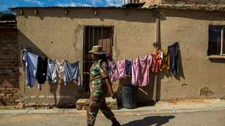 South African National Defence Forces, walks on the street of a densely populated Alexandra township in Johannesburg, South Africa, Thursday, April 16, 2020. South African President Cyril Ramaphosa extended the lockdown by an extra two weeks in a continuing effort to contain the spread of COVID-19 coronavirus. (AP Photo/Themba Hadebe)