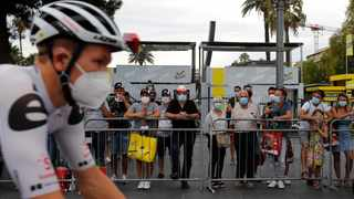 People wear masks as they watch riders prior to the start of the first stage of the Tour de France cycling race. Photo: Christophe Ena/AP