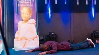 Shepherd Bushiri lies across the alter in front of a poster of his daughter, Israella who died after a battle with a lung illness. Picture: Facebook