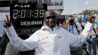 Eliud Kipchoge stands in front of a time board that shows his new world record time of 2:01.39 at the Berlin Marathon. Photo: Markus Schreiber/AP