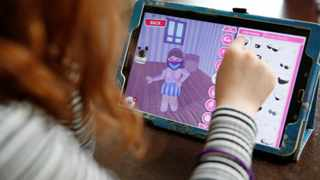 A girl adds a face mask to her character on the game 'Roblox' at her home in Manchester. REUTERS/Phil Noble/File Photo