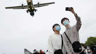 People wearing face masks, as a protection from coronavirus disease take a selfie with a plane that is about to land at Songshan Airport in Taipei, Taiwan. Picture: REUTERS/Ann Wang.