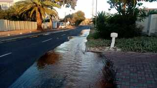 Water streams down South Road after a pipe burst.