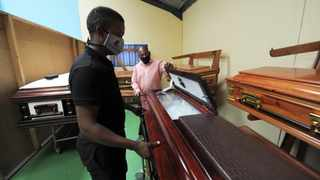Siviwe Mhlomi, the director of Uviwe Funeral Services and Thabo Petrus Klip, working for Mguda Funeral Services, moving coffins around the funeral parlour in Airport Industrial. Photographer: Armand Hough African News Agency(ANA)