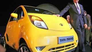 Tata Sons Chairman, Ratan Tata poses alongside the Tata Nano, at its launch in Mumbai, India, Monday, March 23, 2009. Tata Motors launched its snub-nosed, US$2,000 Nano, Monday, in Mumbai, a vehicle meant to put car ownership within reach of millions of the world's poor. The Nano, starting at about 100,000 rupees ($1,980), is 10.2 feet (3.1 meters) long, has one windshield wiper, a 623cc rear engine, and a diminutive trunk, according to the company's Web site. (AP Photo/Gautam Singh)