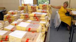 In this file picture marker Elmarie Delport is surrounded by Maths examination scripts. Picture Ian Landsberg