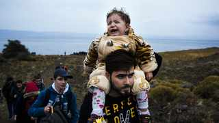 [Picture for illustration] A young girl cries on the shoulders of a man shortly after they arrived with other migrants and refugees on the Greek island of Lesbos after crossing the Aegean sea from Turkey. Picture: Dimitar Dilkoff