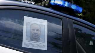 "A police vehicle is seen a poster with a photo of drug lord Joaquin ""El Chapo"" Guzman offering a reward of 60 million Mexican pesos for information along a street in Mexico City. REUTERS/Henry Romero"