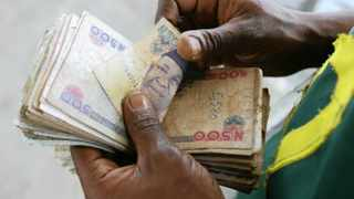 A trader counts a pile of naira notes in Abuja, Nigeria. File picture: Suzanne Plunkett