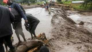 Passengers from stranded vehicles cross floodwaters on foot, on the road from Kapenguria, in West Pokot county, in western Kenya Saturday, Nov. 23, 2019. Kenya's interior minister says dozens of people have been killed in mudslides, after heavy rains unleashed overnight floods in western Kenya. (AP Photo)