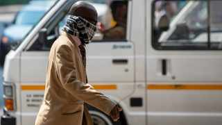 A man using a scarf to cover his face walks along a downtown street Johannesburg, South Africa. Picture: Themba Hadebe/AP