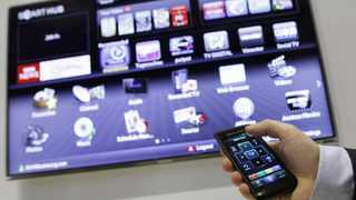 An exhibitor demonstrates a Samsung Smart TV that can be operated with a smartphone.