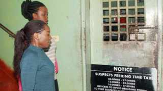 "Zambian Newspaper ""The Post"" managing editor Joan Chirwa-Ngoma, left, and reporter Mukosha Funga, right, are led to detention at Lusaka Central Police on April 12, 2016 in Lusaka. Picture: Dawood Salim / AFP"