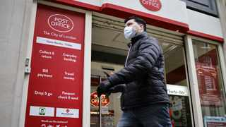 A pedestrian wearing a protective face covering to combat the spread of the coronavirus, passes a Post Office in the City of London. File picture: Tolga Akmen/AFP