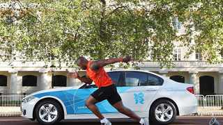 LONDON, UNITED KINGDOM - MAY 13: 100m sprinter Mark Lewis-Francis tests his acceleration against a BMW 320d 'EfficientDynamics' from the London 2012 fleet as part of the BMW London 2012 Performance Series, on The Mall on May 13, 2012 in London, United Kingdom. (Photo by Tom Shaw/Getty Images for BMW)