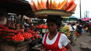 A woman sells skinned pawpaw as she walks in a market on World Food Day in Lagos, Nigeria, on Tuesday, October 16, 2012.