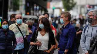 People wearing face masks to prevent the spread of coronavirus queue to buy lottery tickets in downtown Madrid, Spain. Picture: Manu Fernandez/AP