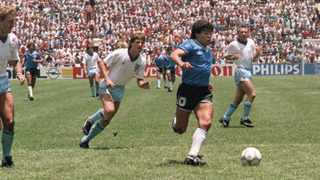 Argentinian forward Diego Maradona runs past English defenders Terry Butcher (L) and Terry Fenwick (2nd L) on his way to score a goal during the World Cup match between Argentina and England in 1986. Picture: AFP