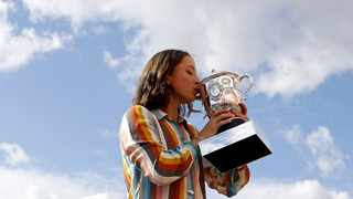 Iga Swiatek of Poland kisses her trophy on the rooftop of the Galerie Lafayette department store one day after winning the French Open at Roland Garros in Paris, France, 11 October 2020. Photo: Ian Langsdon/EPA