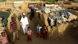 An internally displaced Sudanese family poses for a photograph outside their makeshift shelter within the Kalma camp for internally displaced persons (IDPs) in Darfur. File picture: Mohamed Nureldin Abdallah/Reuters