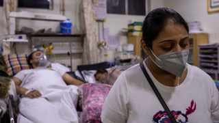 Manika Goel, is seen next to her husband who is suffering from the coronavirus disease (Covid-19) inside the emergency ward at Holy Family hospital in New Delhi. Picture: Danish Siddiqui/Reuters