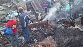 People survey the burnt remains of their homes after a fire razed several shacks at the Cato Crest informal settlement on Sunday. Picture: Supplied.