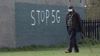"""A man wearing a face mask during an outbreak of coronavirus disease (COVID-19) walks past a graffiti that reads """"STOP 5G"""" in London. Picture: Reuters/Russell Boyce"""