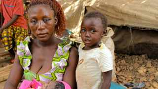 A refugee mother from the Central African Republic sits with her children beside a makeshift shelter in Ndu village, the Democratic Republic of Congo. File photo: UNHCR