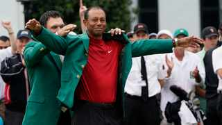 FILE - Patrick Reed helps Tiger Woods with his green jacket after Woods won the Masters golf tournament. Photo: David J. Phillip/AP