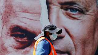 File photo: A worker stands in front of a Blue and White party election campaign banner depicting its leader, Israeli Defence Minister Benny Gantz, alongside Israeli Prime Minister Benjamin Netanyahu. Picture: Reuters