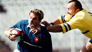 Romania's Solomie George (right) tries ro stop French player Christophe Dominici during the test match between France and Romania in the Dynamo stadium in Bucharest, Romania, 28 May 2000. Photo: EPA/Robert Ghement
