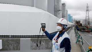 An employee of Tokyo Electric Power Co (TEPCO) uses a geiger counter next to storage tanks for radioactive water at TEPCO's tsunami-crippled Fukushima Daiichi nuclear power plant in Okuma. File picture: Aaron Sheldrick/Reuters