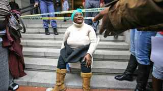 Mandisa Feni of Site C, Khayelitsha, sits on a toilet on the steps of the provincial legislature. Poo protests are political, the writer argues.