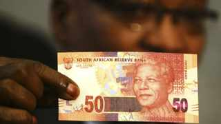 President Jacob Zuma holds up a banknote bearing the face of former president Nelson Mandela. Photo: Reuters