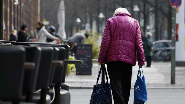 An elderly woman carries shopping bags. File photo: REUTERS, MICHELE TANTUSSI