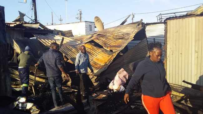 GONE: Residents try to salvage shack. Picture: Nomzamo Yuku