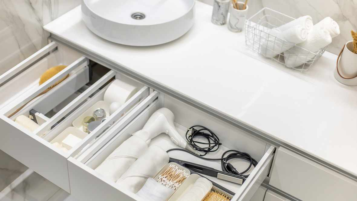 Bathroom under sink organizer drawers with neatly placed bath amenities and toiletries. Table top basin sink with dispenser of liquid soap, toothbrush in cup and group of rolled up white towels.