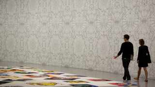 People walk past portraits made from Legos at the preview for Ai Weiwei: Trace at the Hirshhorn Museum in Washington