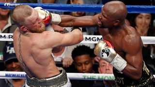 Floyd Mayweather lands a right to the face of Conor McGregor in their fight in August last year. Photo: Eric Jamison/AP