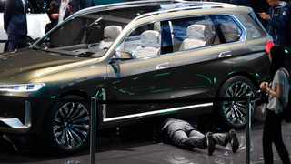 A man crawls underneath a BMW SUV during the first media day of the International Frankfurt Motor Show IAA in Frankfurt, Germany. Photo:  (AP Photo/Martin Meissner)