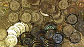 FILE - This April 3, 2013file photo shows bitcoin tokens at 35-year-old software engineer Mike Caldwell's shop in Sandy, Utah. The price of bitcoin, the most widely used virtual currency, rose above US$ 10,000 on Wednesday for the first time, breaking a symbolic threshold in what has been a vertiginous ascent this year. (AP Photo/Rick Bowmer, file)