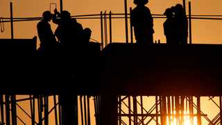 Workers are silhouetted at a building construction site near Phnom Penh, Cambodia, Tuesday, April 3, 2018. (AP Photo/Heng Sinith)