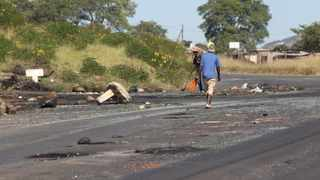 Local youths clear debris at the Slangspruit entry point to Imbali Township on Wednesday, one of the areas where Msunduzi residents protested this week. Picture: African News Agency (ANA)