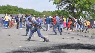 A policeman blocks a stone hurled at him during a protest at Ikemeleng in Kroondal, the police used rubber bullets to dispersed protesters. PHOTO: ANA